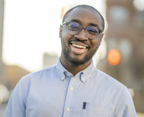 Black man outside, wearing a collared shirt, smiling at the camera