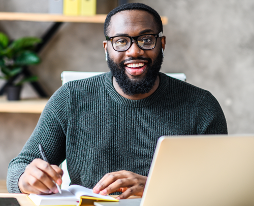 A Black man sitting in front of his laptop, writing but looking up and smiling at the camera