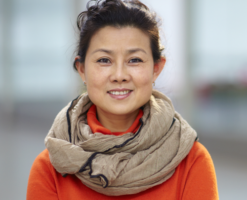 Asian woman outside wearing a pretty scarf smiling at the camera
